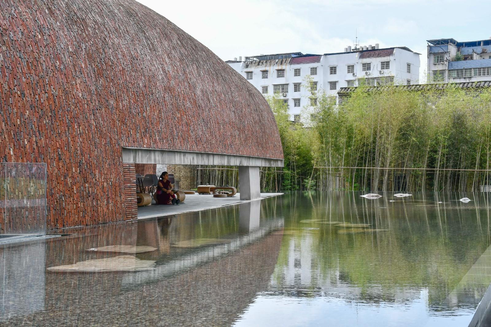 从建筑外观长缝透过水面可见茶室中休憩的人们.jpg